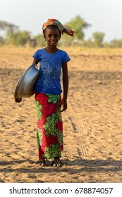 FERLO DESERT, SENEGAL - APR 25, 2017: Unidentified Fulani little girl in headscarf carries a basin. Fulanis (Peul) are the largest tribe in West African savannahs