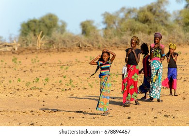 FERLO DESERT, SENEGAL - APR 25, 2017: Unidentified Fulani children in colored clothes play on the street in the village. Fulanis (Peul) are the largest tribe in West African savannahs
