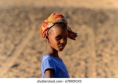 FERLO DESERT, SENEGAL - APR 25, 2017: Unidentified Fulani girl in blue shirt and headscarf walks on the street. Fulanis (Peul) are the largest tribe in West African savannahs