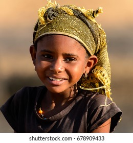 FERLO DESERT, SENEGAL - APR 25, 2017: Unidentified Fulani little girl in headscarf smiles. Fulanis (Peul) are the largest tribe in West African savannahs