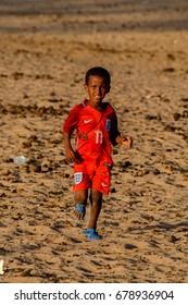FERLO DESERT, SENEGAL - APR 25, 2017: Unidentified Fulani little boy runs along the village. Fulanis (Peul) are the largest tribe in West African savannahs