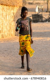 FERLO DESERT, SENEGAL - APR 25, 2017: Unidentified Fulani girl with braids walks along the street. Fulanis (Peul) are the largest tribe in West African savannahs