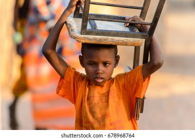 FERLO DESERT, SENEGAL - APR 25, 2017: Unidentified Fulani little boy carries a chair on his head. Fulanis (Peul) are the largest tribe in West African savannahs