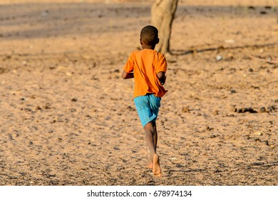 FERLO DESERT, SENEGAL - APR 25, 2017: Unidentified Fulani little boy in orange shirt and blue shorts runs along the street. Fulanis (Peul) are the largest tribe in West African savannahs