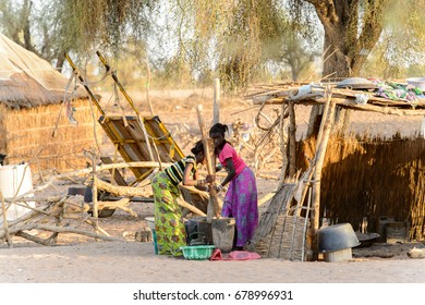 FERLO DESERT, SENEGAL - APR 25, 2017: Unidentified Fulani girls in colored clothes work in the village. Fulanis (Peul) are the largest tribe in West African savannahs