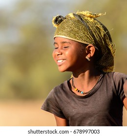 FERLO DESERT, SENEGAL - APR 25, 2017: Unidentified Fulani little girl in headscarf walks along the street. Fulanis (Peul) are the largest tribe in West African savannahs