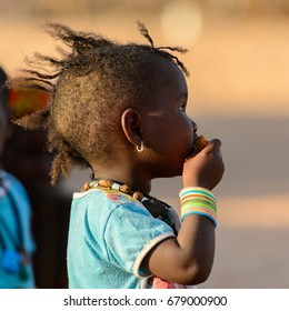 FERLO DESERT, SENEGAL - APR 25, 2017: Unidentified Fulani little girl eats fruit. Fulanis (Peul) are the largest tribe in West African savannahs