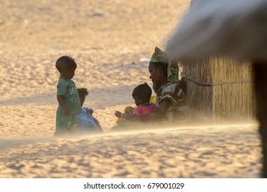 FERLO DESERT, SENEGAL - APR 25, 2017: Unidentified Fulani woman sits near the shack with her children. Fulanis (Peul) are the largest tribe in West African savannahs