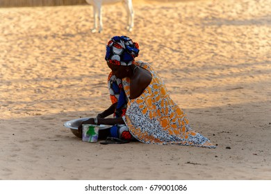 FERLO DESERT, SENEGAL - APR 25, 2017: Unidentified Fulani woman washes dishes on the ground. Fulanis (Peul) are the largest tribe in West African savannahs