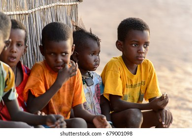 FERLO DESERT, SENEGAL - APR 25, 2017: Unidentified Fulani little children sit near the fence in the village. Fulanis (Peul) are the largest tribe in West African savannahs
