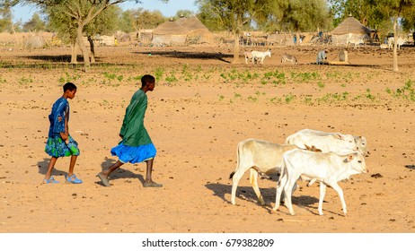 FERLO DESERT, SENEGAL - APR 25, 2017: Unidentified Fulani two boys in colored clothes walk along the street. Fulanis (Peul) are the largest tribe in West African savannahs