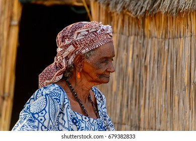 FERLO DESERT, SENEGAL - APR 25, 2017: Unidentified Fulani old woman in colored clothes walks near the shack. Fulanis (Peul) are the largest tribe in West African savannahs
