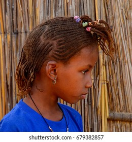 FERLO DESERT, SENEGAL - APR 25, 2017: Unidentified Fulani little girl in blue shirt stands near the shack. Fulanis (Peul) are the largest tribe in West African savannahs