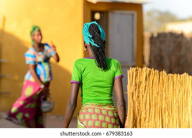 FERLO DESERT, SENEGAL - APR 25, 2017: Unidentified Fulani woman in colored clothes and headscarf walks along the street. Fulanis (Peul) are the largest tribe in West African savannahs