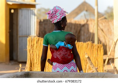 FERLO DESERT, SENEGAL - APR 25, 2017: Unidentified Fulani woman carries a baby on her back. Fulanis (Peul) are the largest tribe in West African savannahs