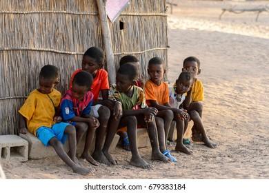 FERLO DESERT, SENEGAL - APR 25, 2017: Unidentified Fulani little children sit on bricks near the fence. Fulanis (Peul) are the largest tribe in West African savannahs