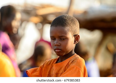 FERLO DESERT, SENEGAL - APR 25, 2017: Unidentified Fulani little boy in orange shirt stands on the street. Fulanis (Peul) are the largest tribe in West African savannahs
