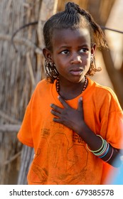 FERLO DESERT, SENEGAL - APR 25, 2017: Unidentified Fulani little girl with braids in orange shirt looks away. Fulanis (Peul) are the largest tribe in West African savannahs