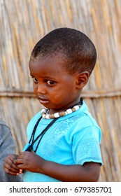 FERLO DESERT, SENEGAL - APR 25, 2017: Unidentified Fulani little boy in blue shirt wears necklace. Fulanis (Peul) are the largest tribe in West African savannahs