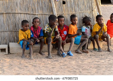 FERLO DESERT, SENEGAL - APR 25, 2017: Unidentified Fulani little children sit on bricks near the fence. Fulanis (Peul) are the largest tribe in West African savannahs