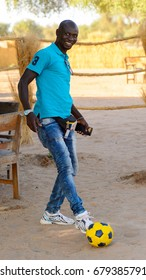 FERLO DESERT, SENEGAL - APR 25, 2017: Unidentified Fulani man in jeans and blue shirt plays football in the yard . Fulanis (Peul) are the largest tribe in West African savannahs