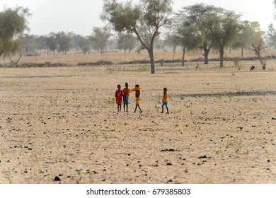 FERLO DESERT, SENEGAL - APR 25, 2017: Unidentified Fulani children play in the middle of the field . Fulanis (Peul) are the largest tribe in West African savannahs