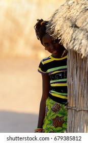 FERLO DESERT, SENEGAL - APR 25, 2017: Unidentified Fulani beautiful girl hides behind the shack. Fulanis (Peul) are the largest tribe in West African savannahs