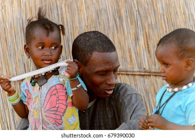 FERLO DESERT, SENEGAL - APR 25, 2017: Unidentified Fulani little girl plays with plastic bag near her father. Fulanis (Peul) are the largest tribe in West African savannahs
