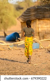 FERLO DESERT, SENEGAL - APR 25, 2017: Unidentified Fulani woman in colored clothes walks along the street. Fulanis (Peul) are the largest tribe in West African savannahs