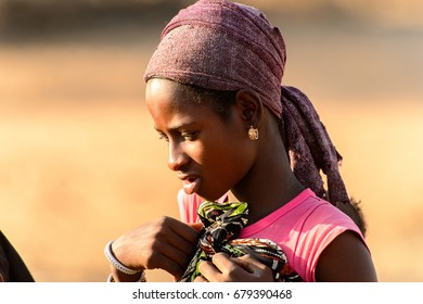 FERLO DESERT, SENEGAL - APR 25, 2017: Unidentified Fulani woman in headscarf stands on the street. Fulanis (Peul) are the largest tribe in West African savannahs
