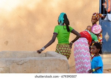 FERLO DESERT, SENEGAL - APR 25, 2017: Unidentified Fulani little girl in blue suit plays on the street. Fulanis (Peul) are the largest tribe in West African savannahs