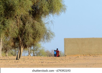 FERLO DESERT, SENEGAL - APR 25, 2017: Unidentified Fulani people walk in the village . Fulanis (Peul) are the largest tribe in West African savannahs
