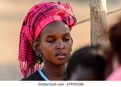 FERLO DESERT, SENEGAL - APR 25, 2017: Unidentified Fulani girl in colored headscarf looks down. Fulanis (Peul) are the largest tribe in West African savannahs