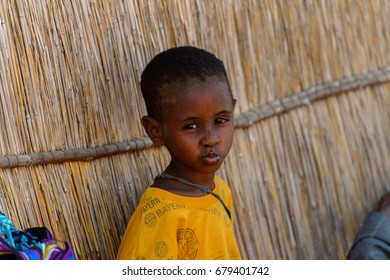 FERLO DESERT, SENEGAL - APR 25, 2017: Unidentified Fulani little boy leans on the shack. Fulanis (Peul) are the largest tribe in West African savannahs
