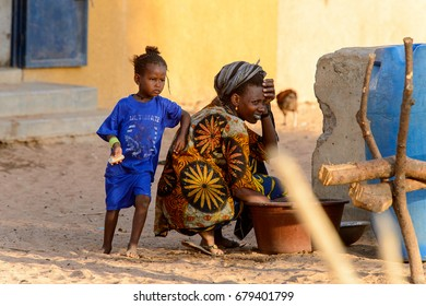FERLO DESERT, SENEGAL - APR 25, 2017: Unidentified Fulani woman squats near the basin with a little girl nearby . Fulanis (Peul) are the largest tribe in West African savannahs