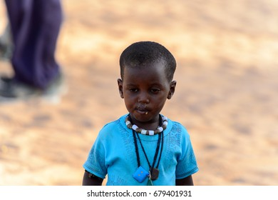 FERLO DESERT, SENEGAL - APR 25, 2017: Unidentified Fulani little boy stands in the middle of the street. Fulanis (Peul) are the largest tribe in West African savannahs