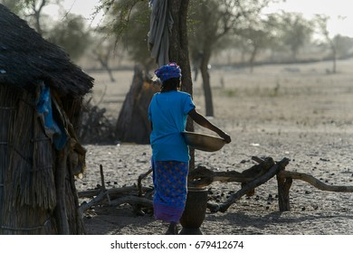 FERLO DESERT, SENEGAL - APR 25, 2017: Unidentified Fulani woman in blue shirt holds a basin in her hands. Fulanis (Peul) are the largest tribe in West African savannahs