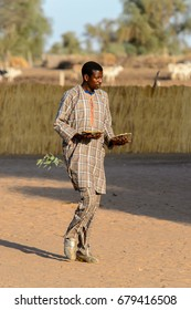FERLO DESERT, SENEGAL - APR 25, 2017: Unidentified Fulani man walks along the street. Fulanis (Peul) are the largest tribe in West African savannahs