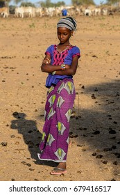 FERLO DESERT, SENEGAL - APR 25, 2017: Unidentified Fulani girl in colored clothes and headscarf walks along the street. Fulanis (Peul) are the largest tribe in West African savannahs