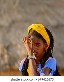 FERLO DESERT, SENEGAL - APR 25, 2017: Unidentified Fulani woman with braids in yellow headscarf walks along the street. Fulanis (Peul) are the largest tribe in West African savannahs