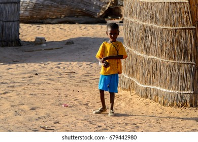 FERLO DESERT, SENEGAL - APR 25, 2017: Unidentified Fulani little boy stands in the middle of the yard. Fulanis (Peul) are the largest tribe in West African savannahs