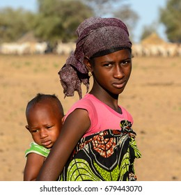 FERLO DESERT, SENEGAL - APR 25, 2017: Unidentified Fulani girl in colored clothes and headscarf carries a baby on her back. Fulanis (Peul) are the largest tribe in West African savannahs