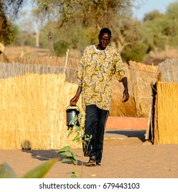 FERLO DESERT, SENEGAL - APR 25, 2017: Unidentified Fulani man carries a kettle in his hand. Fulanis (Peul) are the largest tribe in West African savannahs