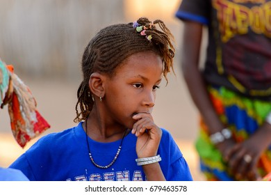 FERLO DESERT, SENEGAL - APR 25, 2017: Unidentified Fulani little girl in blue shirt looks away. Fulanis (Peul) are the largest tribe in West African savannahs