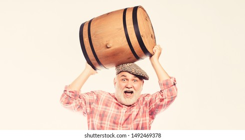 Fermentation product. Retro man with a beer barrel. Barman. wooden barrel. oktoberfest festival. brewery for maturing alcohol. Homemade wine. Man bearded senior carry wooden barrel for wine.