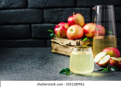 Fermented apple drink and fresh apples in wooden box on concrete background. Selective focus, space for text.