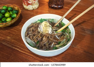 Fermented balut egg in a bowl. An exotic soup with Pho noodles on the table in the restaurant. Street food Vietnamese traditional cuisine.