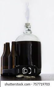 Fermented beer in a demijohn with airlock and hand capper with dark brown bottles and caps and over white background