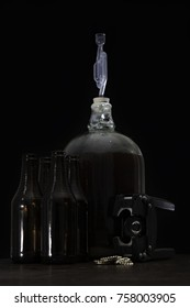 Fermented beer in a demijohn with airlock and hand capper with dark brown bottles and caps and over black background