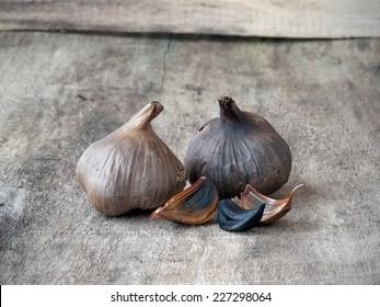 Fermented black garlic bulbs and cloves on wood